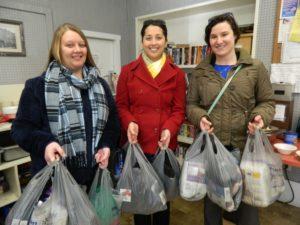 three volunteers donating needed supplies