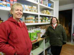 two volunteers stocking food shelves